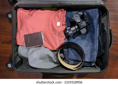 Flatlay of Open travel suitcase with clothes camera and passport on the  wooden background