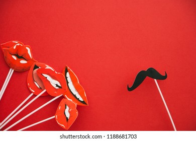 flatlay overhead top black paper photo booth props lip and mustache red background copy space.