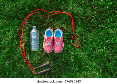 Flatlay with pair of pink girl sneakers shoes, jump rope and bottle of water in green grass outside, view from above top. Activity recreation concept. Healthy lifestyle.