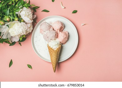 Flatlay of pastel pink strawberry and coconut ice cream scoops, sweet cones on white plate and white peonies over pastel pink background, top view, copy space