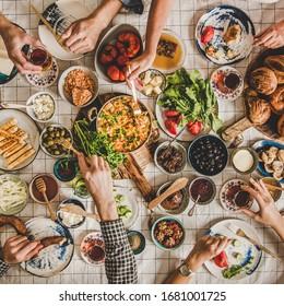 Plat-lay of people mains prenant des viennoiseries turques pour le petit-déjeuner, légumes, verts, fromages, oeufs au plat, confitures, thé dans des lunettes de tulipe sur une nappe de lin à plaques, vue de dessus, culture carrée
