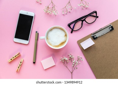 Flatlay pink background office home working space with coffee, paper holder, stickers and phone