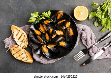 Flat-lay plate of cooked mussels and cutlery