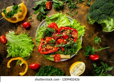 Flatlay plate of fresh vegetarian salad with tomatoes, corn, beans, pepper and parsley at golden textured decorated with vegetables table background.