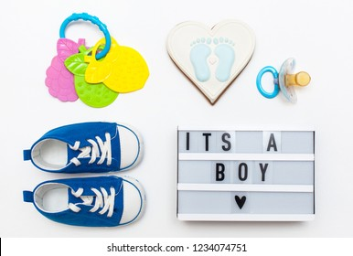"flatlay pregnancy composition. top view of children's accessories: toys, pacifier, rattle, baby projector lamp ""it's a boy"", a cotton flower and delicious gingerbread"