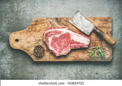 Flat-lay of raw prime beef meat dry-aged steak rib-eye on bone with seasoning and chopper on wooden cutting board over grey concrete background, top view. Meat high-protein dinner concept