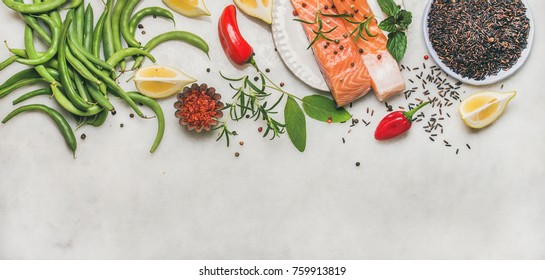 Flat-lay of raw salmon fish fillet steaks with vegetables, greens, rice and spices over grey background, top view, copy space. Clean eating, alkaline diet, dieting, power boosting, vegetarian concept
