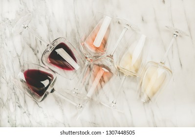 Flat-lay of red, rose and white wine in glasses over grey marble background, top view. Bojole nouveau, wine bar, winery, wine degustation concept