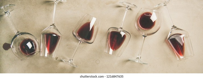 Flat-lay of red wine in glasses over grey concrete background, top view, copy space, wide composition. Bojole nouveau, wine bar, winery, wine degustation concept