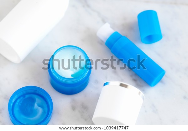 Flatlay skincare cosmetic products in blue and white packaging on white  marble table. Cream, serum, toner,  lotion.