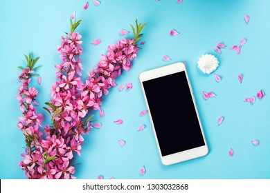 Flatlay with smartphone mock up and flowers. Floral pattern at blue background. Top view. Flowers composition. Spring background with mobile phone. Copy space. Spring pink flowers
