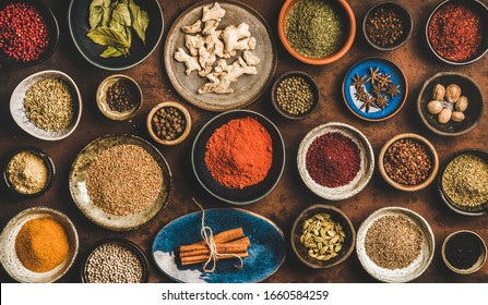 Flat-lay of spices in bowls and plates over rusty background, top view. Black pepper, allspice, cloves, thyme, cumin, sesame, star anise, ginger, cinnamon, cardamom, mahlep, smoked salt, rosemary, bay