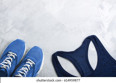 Flatlay sport composition with blue sneakers and t-shirt on gray concrete background. Concept healthy lifestyle, sport, training in gym, diet. Horizontal orientation, top view, place for copyspace.