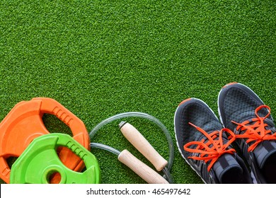 Flatlay of sport equipments on the green grass with copy space for putting texts and content. The set of sport equipments comprises sneakers, weights, and a jumping rope.