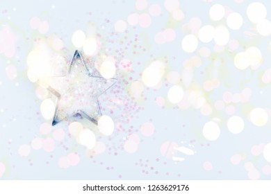 Flatlay with star cookie cutter and snowflake sprinkles on blue background. Holiday, Christmas and New Year concept. Cozy homey details. Horizontal, bright lights bokeh background