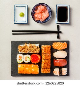 Flat-lay of sushi set on grey concrete background, square composition