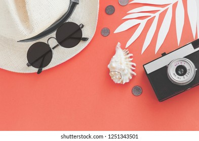 Flatlay traveler accessories on yellow background with palm leaf, coin, shell, old camera and sunglasses. Top view travel or vacation concept and Summer background. Color of the year 2019 Living coral