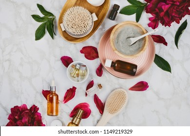 Flatlay of various beauty, bath and SPA products (serum, clay, essential oils, body brush, cream etc) and peony flower and petals on a marble background