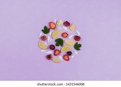 Flatlay with various fruits, berries and flowers on violet