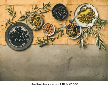 Flat-lay of various kinds of Mediterranean pickled olives in plates and bowls and olive tree branches on yellow linen cloth over concrete background, top view, copy space. Mediterranean meze appetizer