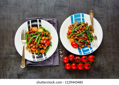Flat-lay of vegan beans salad in plates with micro greens, tomatoes and aspargus. Healthy energy boosting salad on dark background. Clean eating, superfood, vegan, detox food concept. Top view
