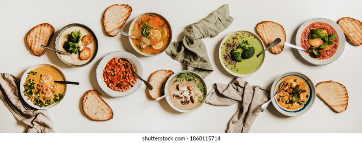 Flat-lay of vegetarian creamy homemade soups variety with bread slices over white plain background, top view. Autumn and Winter creamy vegan soups, fall and winter vegetarian food menu concept