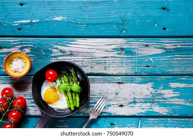 Flat-lay of vegetarian healthy breakfast with fried eggs, green aspargus and fresh tomatoes in vintage cast iron pan on turquoise vintage table from above. Clean eating, diet food concept