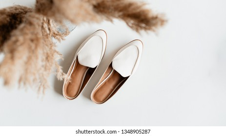 Flatlay of white shoes on white surface.