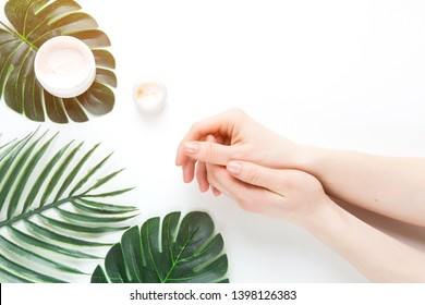 Flatlay. Woman putting nutritious cream on her hands on white background among jar of cosmetic cream, leaf palm branch. Final stage of manicure: woman uses moisturizer for the skin. Copy space
