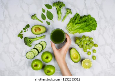 Flatlay with woman's hand reaching for green juice surrounded by green fruits and vegetables on marble table