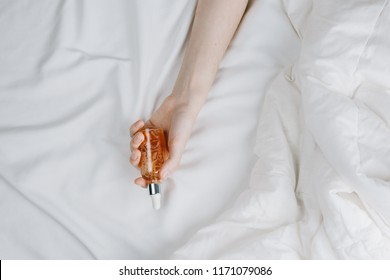 Flatlay of woman's hands in bed holding bottle with serum, beauty and skincare concept