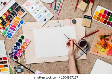 Flatlay with woman's hands holding brush, pallets, pencils, watercolors and other stationary supplies, artist or designer workplace
