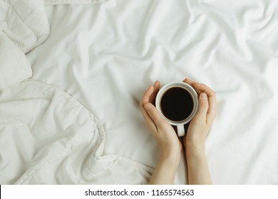 Flatlay of woman's hands holding cup of coffee in bed on white sheets, morning concept
