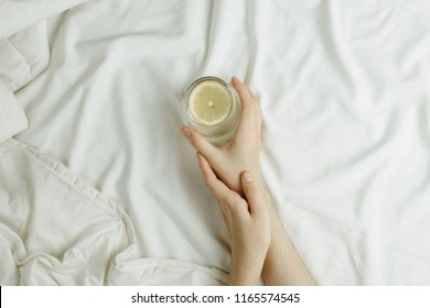 Flatlay of woman's hands holding glass in lemon water in bed on white sheets, healthy morning concept