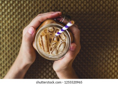 Flatlay of woman's hands holding mason jar with iced tea or coffee, selective focus