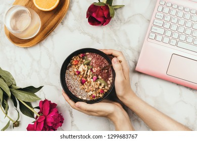 Flatlay of woman's hands holding smoothie bowl with laptop, peonies and water on marble table
