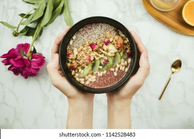 Flatlay of woman's hands holding vegan smoothie bowl with chia pudding topped with granola, kiwi, pine nuts and rose buds with peony flower, lemon water and spoon on marble table, healthy breakfast