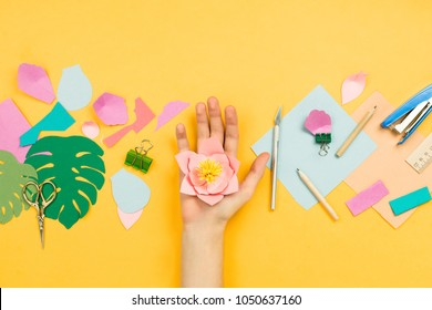 Flatlay with woman's hands making beautiful floral papercraft with other art and stationary accessories. Concept of hobby, education or creativity