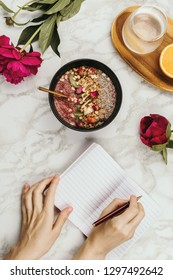 Flatlay of woman's hands with notebook and smartphone, vegan smoothie bowl with chia pudding topped with granola, kiwi, pine nuts and rose buds and peon flowers on marble, healthy breakfast concept