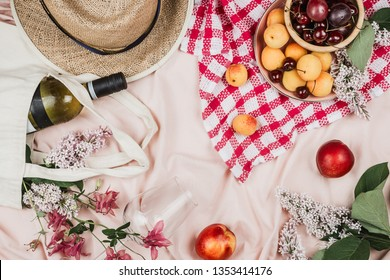 Flatlay of woman's hat, fruits, wine and flowers on peachy blanket, summer picnic concept