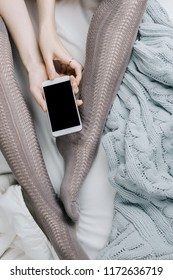 Flatlay of woman's legs in grey stocking holding smartphone with black screen in bed