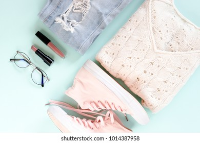 Flatlay of women clothes, cosmetics, accessories on a pale mint pastel background. Lifestyle concept