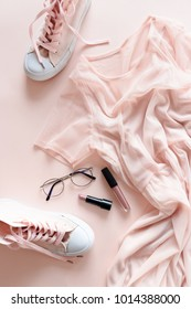 Flatlay of women clothes, cosmetics, accessories on a pale pink pastel background. Lifestyle concept