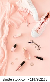 Flatlay of women dress, sneakers, cosmetics and accessories on a pink pastel background