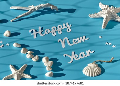 flatlay: The words 'Happy New Year' are written with white letters on blue background. Paper flatlay with shallow depth of fields, symbols of the sea like shells, starfish and stones decorate the scen