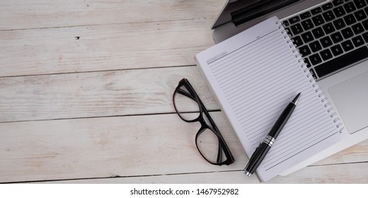 Flatlay work space laptop with blank note book on white wooden background  with copy space, banner concept