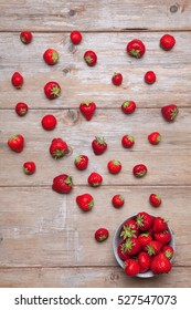 Flatlays. Top view of fresh strawberries scattered and in a plate on a wooden surface