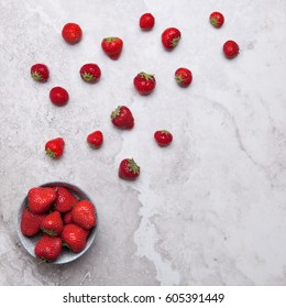 Flatlays. Top view of fresh strawberries scattered and in a plate on a marble surface