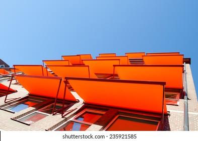 Flats windows with orange shade sail sun protection.