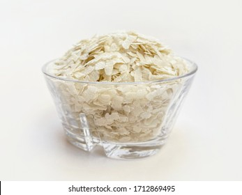 flattened rice flakes in glass bowl isolated on white. Flattened rice commonly known as Avalakki in Kannada